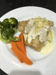 Hake with a cheesy sauce, mash and veg